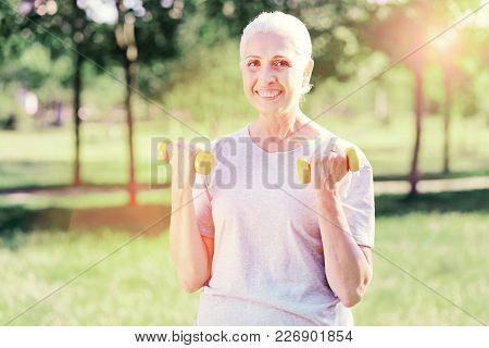 Beauty Never Fading. Portrait Of Smiling Elderly Woman Holding Weights In Both Hands While Showing C