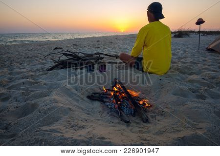 Adventurer Sits Next To Burning Bonfire On The Beach, Admires Sunset Over The Sea And Going To Drink