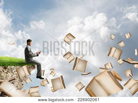 Young Businessman Floating On Island In Blue Sky With Smartphone In Hands
