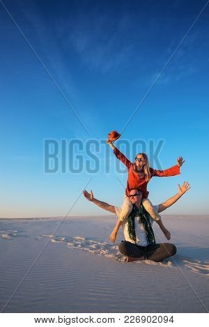 Funny Couple, Man With A Laughing Girl On His Shoulders Sits In The Desert On A Sunny Evening, Fools