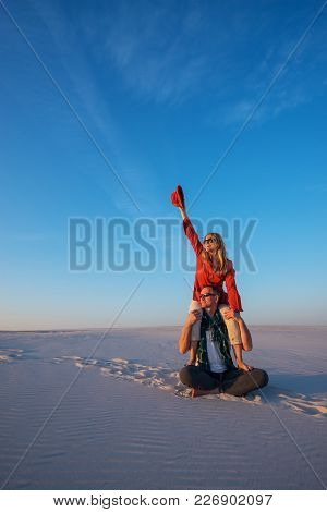 Romantic Couple, Man With A Laughing Girl On His Shoulders Sits In Desert On A Sunny Evening, Fools