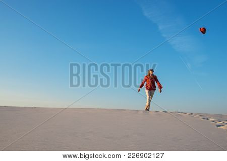 Joyful Young Woman, Blonde Runs In The Desert, Catches Her Flying Hat In The Blue Sky And Has Fun. H