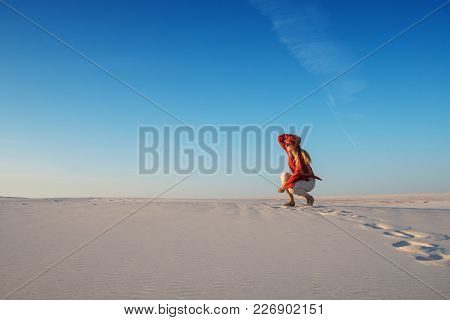 Modern Young Woman, Blonde Poses In The Desert, Admires Magic Landscape And Dreams On Sunny Evening.