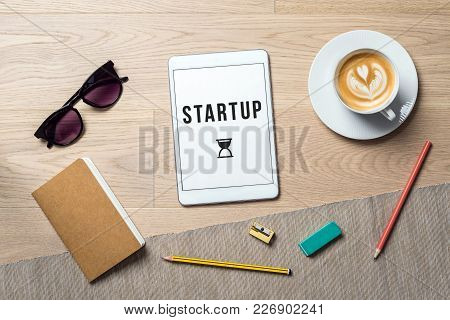 Startup Writing On Tablet Screen With Notebook And Glasses Lying On Wooden Office Desk As Flat Lay