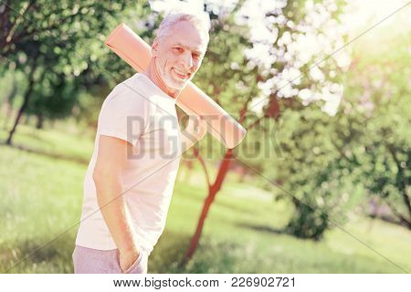 Having Rest. Waist Up Of Elderly Man Caring Ground Pan On His Shoulder While Standing And Looking At