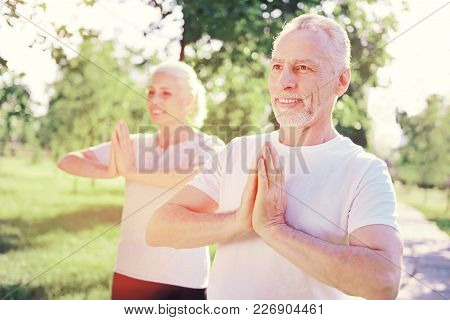 Mental Equilibrium. Close Up Of Smiling Friends Doing Yoga In Fresh Air While Looking Away And Expre