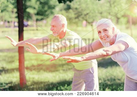 Having Interest. Amused Friends Doing Exercises In The Park While Being Concentrated And Having Opti