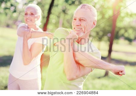 Useful Exercises. Waist Up Of Optimistic Elderly Family Stretching Arms While Standing In Nature Sur