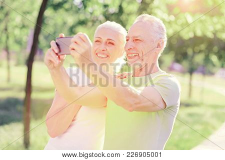 Sweet Memory. Portrait Of Elderly Family Expressing Cheer While Using Mobile Phone And Making Selfie
