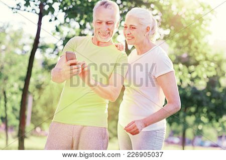 Look Here. Waist Up Of Positive Friends Using Mobile Phone And Expressing Interest While Standing In