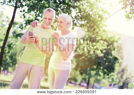 Splendid Mood. Positive Elderly Family Keeping Mobile Phone In Hands While Standing Closely And Expr