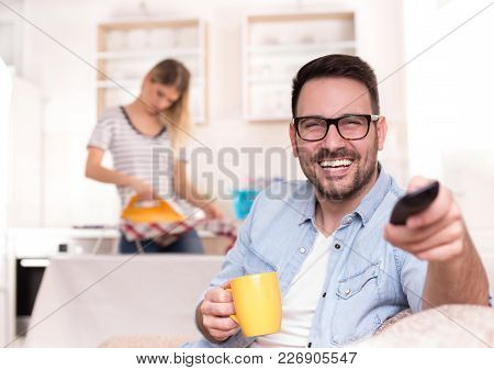 Man Watching Tv And Woman Doing Housework