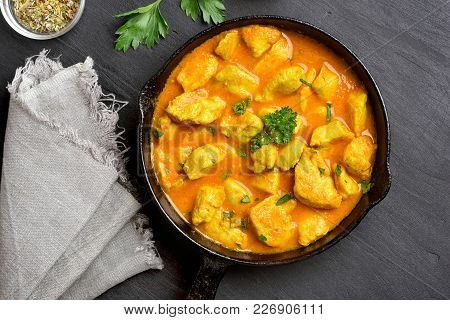 Chicken Curry In Frying Pan On Dark Stone Background. Top View, Flat Lay.