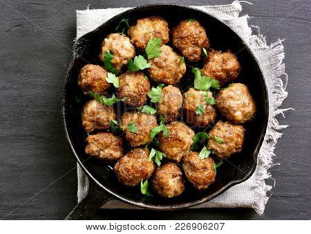 Delicious Meatballs In Frying Pan On Black Stone Background. Top View, Flat Lay