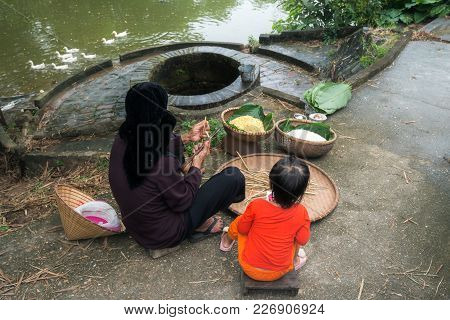 Grandmother And Her Granddaughter Wrapping Chung Cake, The Square Shape Cake, By Old Well And Pond.
