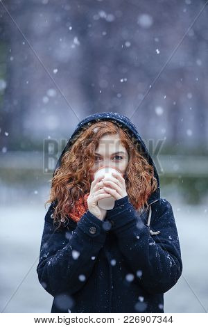 Portrait Of An Exotic Red Hair Woman Drinking A Hot Beverage Under The Snow