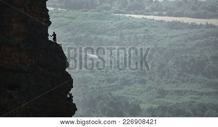 Long Shot Of Climbers Hanging By A Cliff Against Land