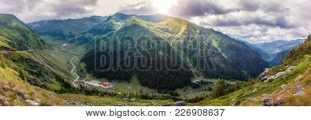 Majestic Mountain Scenery. Mountain Hills Glowing In Sunlight Over Highway In Mountains And Overcast