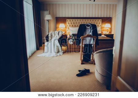 Wedding Dress, Suit And Bouquet In The Hotel Room Accecories