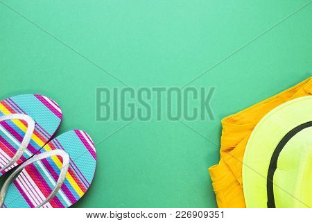 Seaside Concept Outfit - Beach Sleepers And A Bright Hat On A Pile Of Clothes On Green One-color Bac