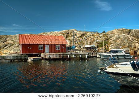 Marine Lodge Of Red Color On The Rocky Coast Of A Swedish Island. Yachts Near The Coastline.