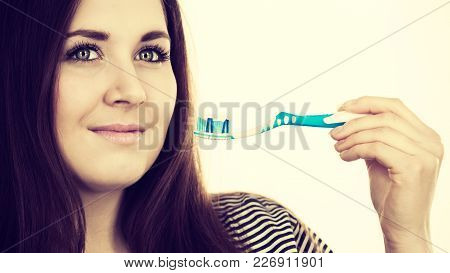 Woman Holding Toothbrush With Paste On It. Smiling Positive Girl Ready To Cleaning Teeth. Oral Hygie