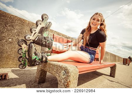 Happy Joyful Young Woman Wearing Roller Skates Sitting On Bench Enjoying Herself. Female Being Sport
