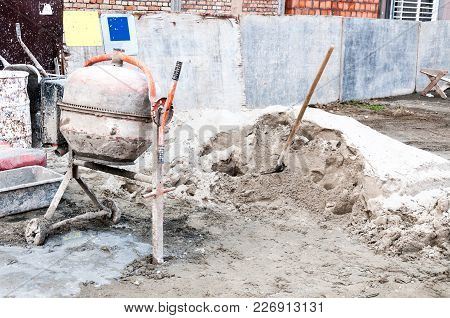 Small Construction Work Site With Dirty Plaster Mixer, Shovel Stick In The Pile Of Sand And Bags Of