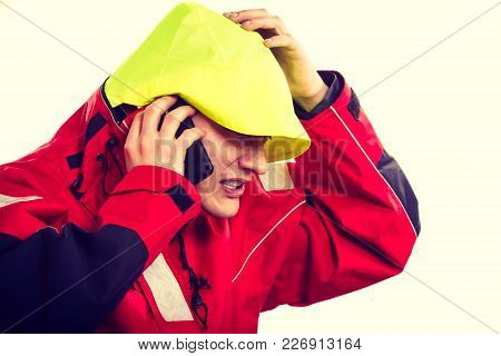 Man In Hood With Phone. Young Male In Waterproof Coat Talking On Cellphone. Adventure Danger Connect