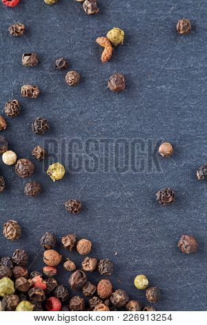 Black, Red And White Peppercorns Isolated On Dark Background. Heap Of Spice. Mix Of Different Pepper
