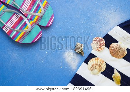 Seaside Relaxing Voyage. Blue Powdered Background With Beach Clothing And Slippers. Travel Or Touris
