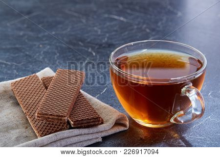 A Transparent Glass Cup Of Black Tea With Waffles On The Light Grey Cotton Napkin On A Dark Greyish