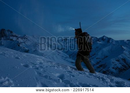 Brave Traveler Lights The Way With A Headlamp At Night Winter Mountain. Snowboarder With Backpack An