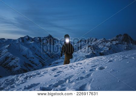 Brave Explorer With Headlamp Commits A Night Climb To A Steep Snowy Mountain. Wearing Ski Wear And B