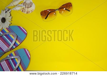 Yellow One-coloured Background With Sunglasses, And Beach Slippers, Top View. Voyage Concept. Space