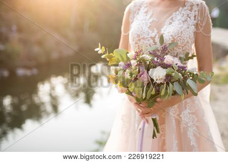 The Bride In A Beige Wedding Dress Holding A Lush Bridal Bouquet Of Lilac Roses And A Lot Of Greener