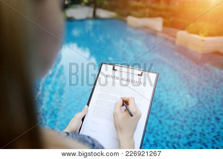 Close Portrait Of Signing Rental Agreement Document On Background Of Swimming Pool. Woman Taking Apa