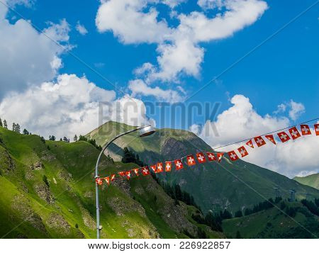 Swiss National Flag Garland Against The Swiss Alps At Samnaun, Switzerland, Beautiful Clouds And Bri