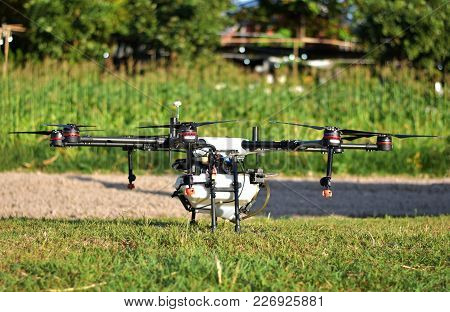 Agriculture Drone, Photo Image Of Agriculture Drone Carry A Tank Of Liquid Fertilizer Parking On Gre