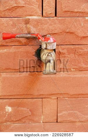 Faucet On Brick Wall Background At Home