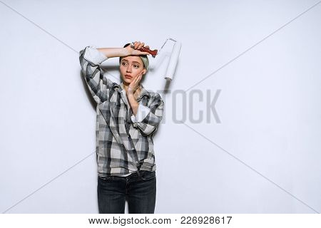 Tired Young Girl In A Plaid Shirt Makes Repairs, Paints The Walls With A Roller
