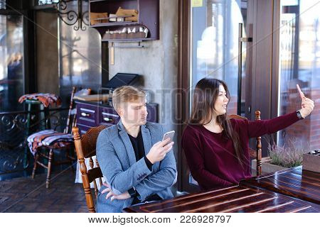 Physicist With Smartwatch On Hand In Cafe With Colleague Taking Selfies Using Smartphone Wait Friend