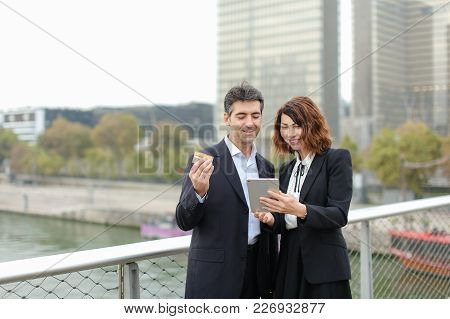 Strict Dressed Man And Woman Buy Goods By Credit Cart In Tablet. Couple Walking In City Center. Wife