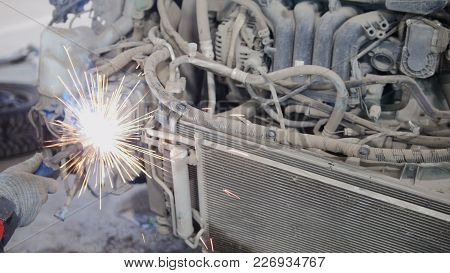 Industrial Concept: Worker Doing Welding In Car Auto Service, Close Up Shot