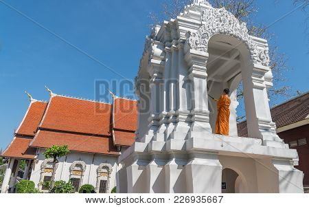Chiang Mai Thailand - January 29 2018; Buddhist Monk In Orange Robes  With Orange Roof Beyond Stands