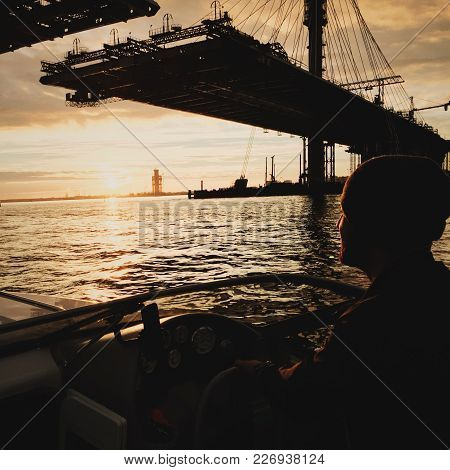Man Sitting In Motorboat And Looking At Building Bridge In Sunset Lights.