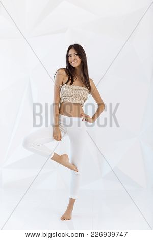 Attractive Fitness Asian Woman Indoors On White Abstract Polygon Background. Casual Mixed-race Asian