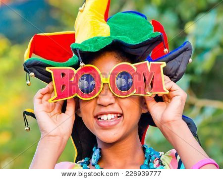Young Girl Smiling With Colorful Clown Hat And Funny Glasses