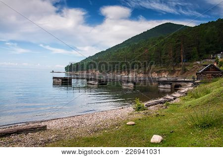 Idyllic View Of The Wooden Pier In The Lake With Mountain Scenery Background. Lake Baikal In The Day