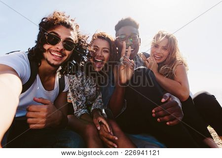 Excited Young Friends Taking Selfie Outdoors. Diverse Group Of Men And Women Sitting Together And Ta